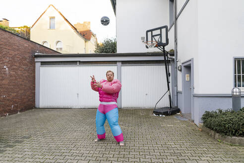 Portrait of a man with basketball wearing pink bodybuilder costume - GUSF03230