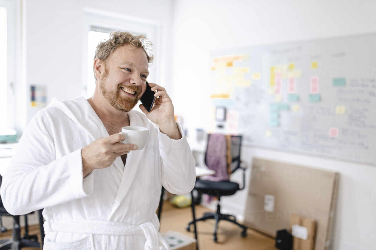Businessman wearing bathrobe in office talking on the phone - GUSF03236 - Gustafsson/Westend61