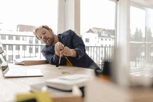 Businessman playing golf on desk in office - GUSF03239