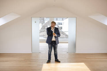 Businessman standing in empty apartement looking around - GUSF03242