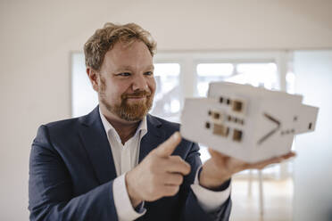 Businessman holding architectural model in office - GUSF03245