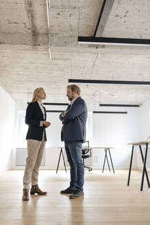 Businessman and businesswoman talking in office - GUSF03272