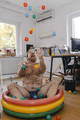 Crazy businessman sitting in wading pool in office playing with balls - GUSF03284