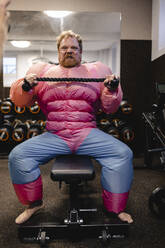 Man wearing pink bodybuilder costume practicing in gym - GUSF03287