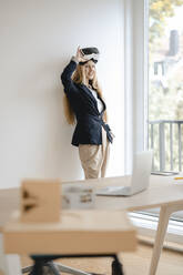 Smiling young businesswoman wearing VR glasses in office - GUSF03305