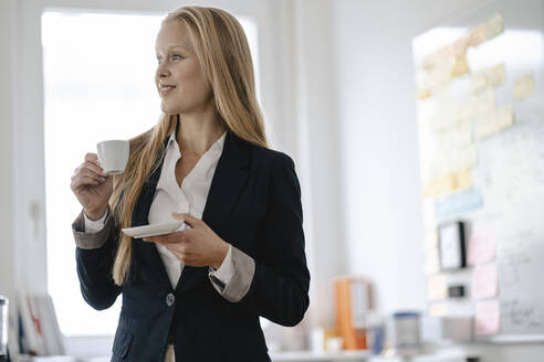Young businesswoman having a coffee break in office - GUSF03314