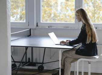 Young businesswoman using laptop on table tennis table in office - GUSF03323