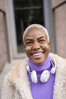 Portrait of mature white haired woman with white headphones and stickers in her face, good vibes - AFVF05013