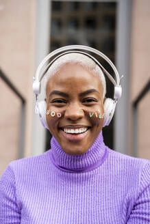 Portrait of white haired woman with white headphones and stickers in her face, good vibes - AFVF05025