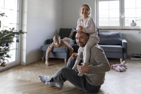 Portrait of mature man sitting on the floor at home playing with his little daughter - KMKF01203
