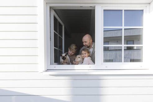 Father with his two children, dog and cat at opened window of their house - KMKF01212