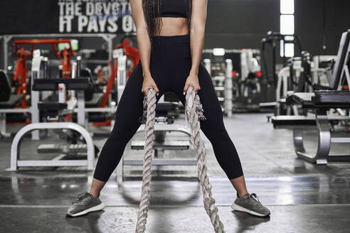 Female athlete doing strength training with heavy ropes in gym - VEGF01481