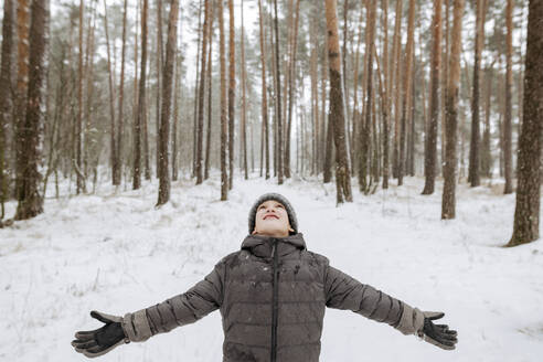 Russia, Ryazan, boy catching snowflakes in winter forest - EYAF00837