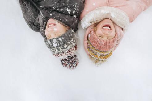 Portrait of two siblings lying on snow - EYAF00852