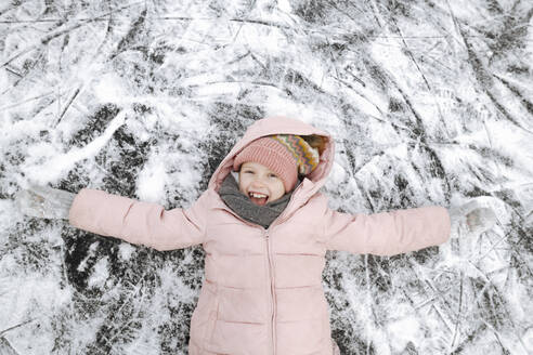 Portrait of happy girl with arms outstretched lying on ice - EYAF00861
