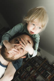 Father carrying little daughter on his shoulders at home - IHF00259