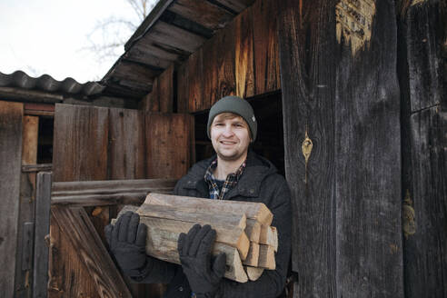 Portrait of smiling man carrying firewood - EYAF00872