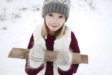 Portrait of smiling girl carrying firewood in winter - EYAF00875