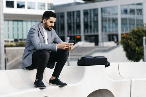 Casual young businessman sitting on a bench in the city using cell phone - JRFF03990
