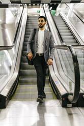 Casual young businessman on escalator - JRFF03996