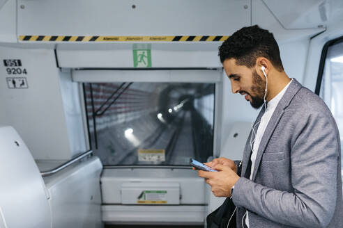 Young businessman with cell phone and earphones on the subway - JRFF04005