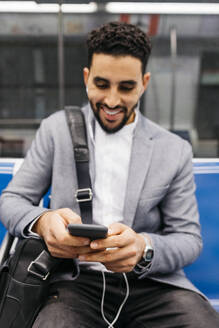 Smiling young businessman with cell phone and earphones on the subway - JRFF04008