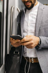Close-up of businessman using cell phone on the subway - JRFF04014