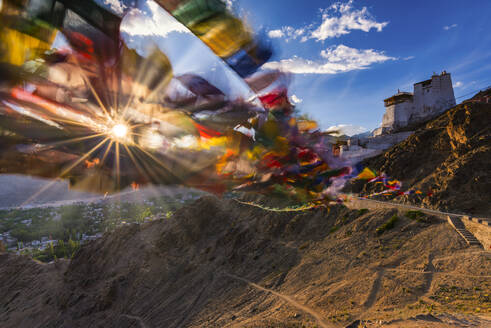India, Jammu and Kashmir, Leh, Setting sun shining through prayer flags ofNamgyal Tsemo Monastery - WGF01314
