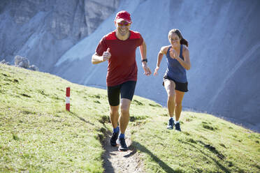 Man and woman running uphill in the mountains - CVF01551