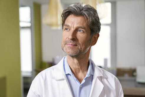 Portrait of confident doctor in his medical practice looking away - PHDF00038
