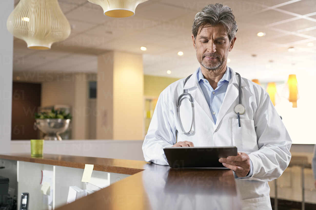 Doctor using tablet at reception in his medical practice - PHDF00044 - Isabella Bellnini/Westend61