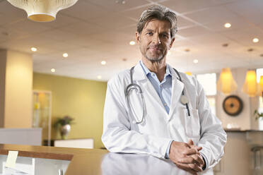 Portrait of confident doctor at reception in his medical practice - PHDF00047