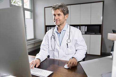 Doctor using computer at desk in his medical practice - PHDF00050