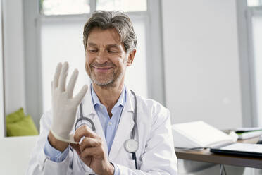 Doctor putting on protective gloves in his medical practice - PHDF00056
