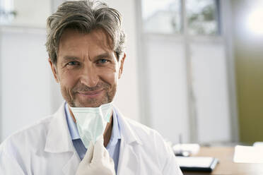 Portrait of smiling doctor with mask in his medical practice - PHDF00062