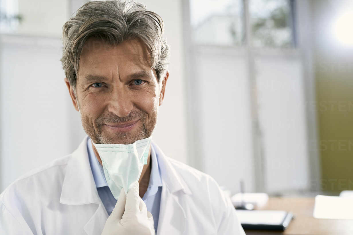 Portrait of smiling doctor with mask in his medical practice - PHDF00062 - Isabella Bellnini/Westend61