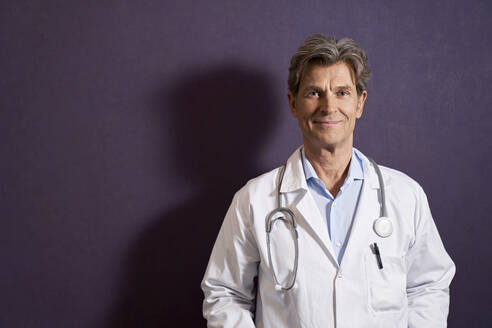 Portrait of confident doctor in front of a purple wall - PHDF00068