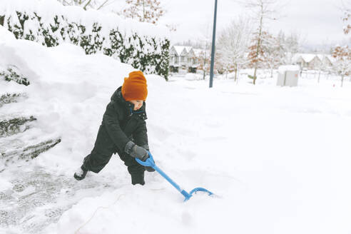 Canada, British Columbia, Vancouver, boy shovelling snow, winter fun - CMSF00073