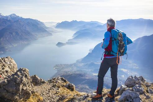 Hiker standing on mountain, looking at Lake Como, Italy - MCVF00192