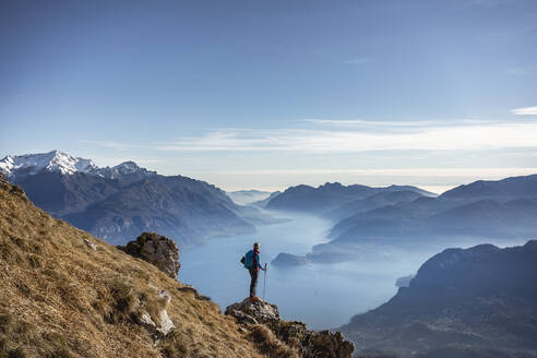 Hiker standing on mountain, looking at Lake Como, Italy - MCVF00195