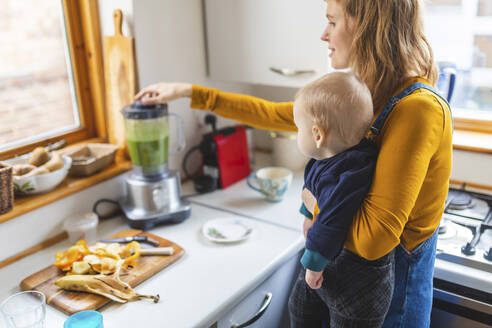 Woman in the kitchen preparing healthy smoothie and holding her baby son - WPEF02455