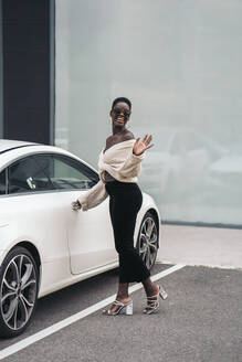 Portrait of young woman posing in front of sports car - MPPF00456