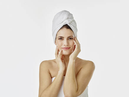 Portrait of smiling woman with hairs wrapped in towel against white background - RORF01991