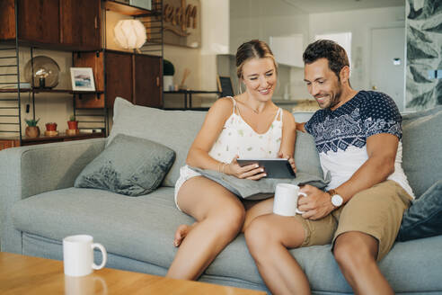 Happy relaxed couple sitting on couch in living room sharing a tablet - MPPF00458