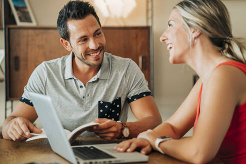 Happy couple sitting at table with laptop and book - MPPF00467