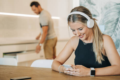 Smiling woman sitting at table with headphones and smartphone - MPPF00482