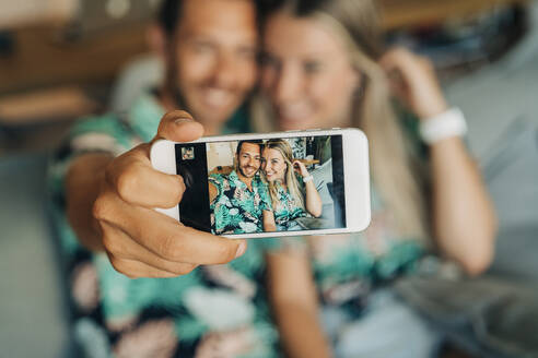 Happy couple sitting on couch in living room wearing Hawaiian shirts taking a selfie - MPPF00488