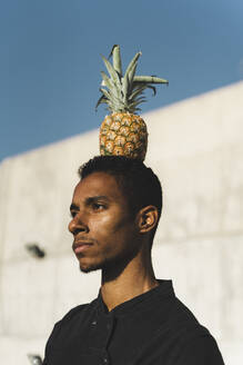 Portait of a young man balancing a pineapple on his head - AFVF05125