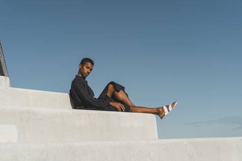 Young man wearing black kaftan sitting on concrete stairs under blue sky - AFVF05155