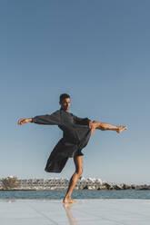 Young man wearing black kaftan performing at the waterfront - AFVF05200